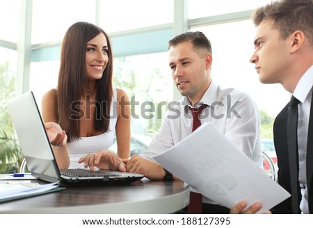 Image of businesswoman pointing at document in laptop while interacting with his partner at meeting  - stock photo