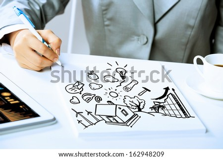 Image of businesswoman sitting at table and drawing sketch