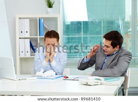 Image of businesswoman sneezing while her partner looking at her unsurely in office - stock photo