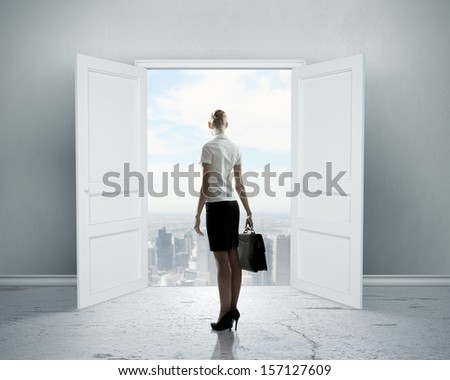 Image of businesswoman standing in front of opened door - stock photo