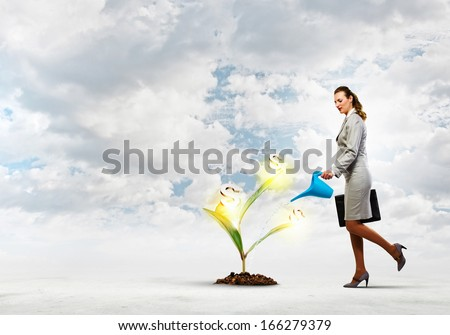 Image of businesswoman watering money tree with pot