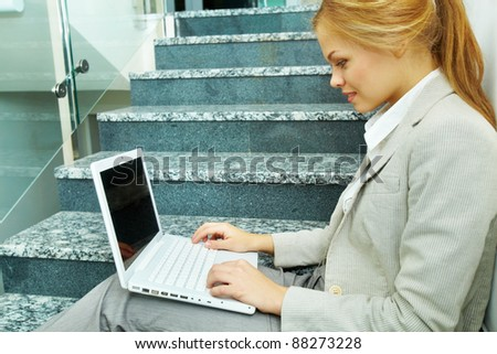 Image of businesswoman with laptop working on staircase - stock photo