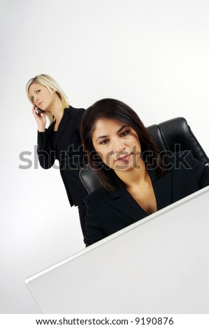 Image of businesswomen at work on computer and phone