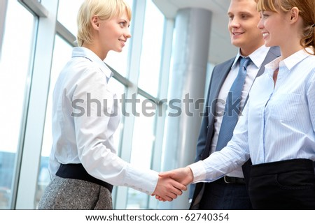 Image of businesswomen handshake after signing new contract - stock photo