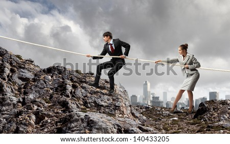 Image of busionessman and businesswoman pulling rope atop of mountain - stock photo