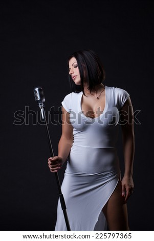 Image of busty slim singer posing in studio - stock photo