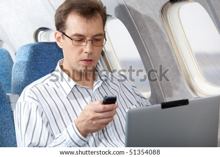 Image of busy businessman working during flight - stock photo