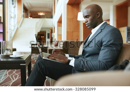 Image of busy young businessman working on laptop. African businessman sitting in hotel lobby waiting for someone. - stock photo