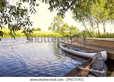 Image of canoes by the river.  - stock photo