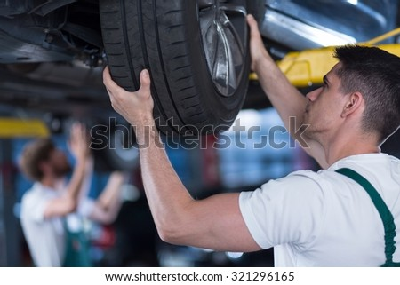Image of car mechanic checking wheel of lifted vehicle - stock photo
