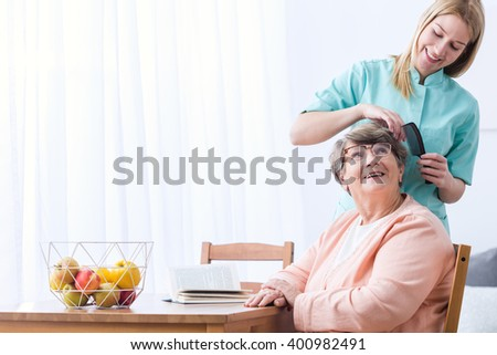 Image of caregiver take care of senior patient - stock photo