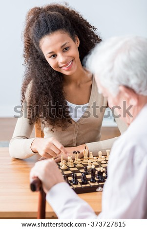 Image of carer and disabled senior with hobby - stock photo