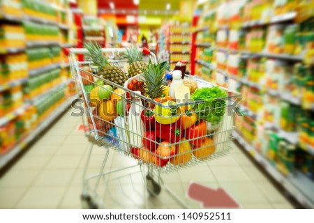 Image of cart full of products in supermarket - stock photo