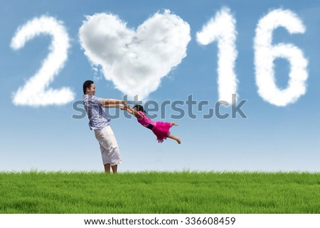 Image of cheerful father playing with his daughter on the meadow under cloud shaped numbers 2016