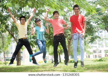 Image of cheerful friends jumping together in the park - stock photo