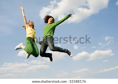 Image of cheerful girl and guy jumping high against bright blue sky and laughing - stock photo