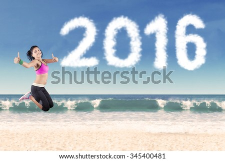 Image of cheerful indian woman jumping on the beach while showing thumbs up with clouds shaped number 2016 - stock photo