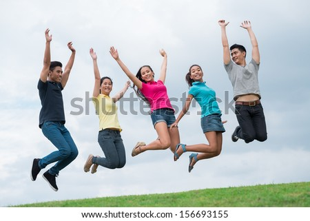 Image of cheerful jumping students outside - stock photo