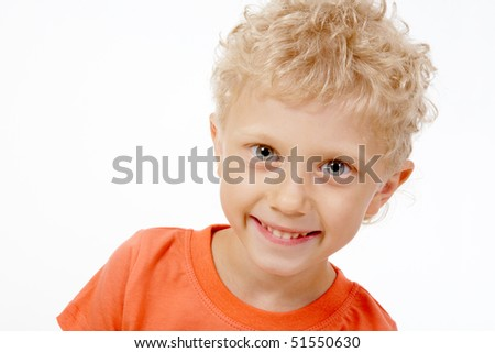 Image of cheerful little boy with curly hair looking at camera - stock photo