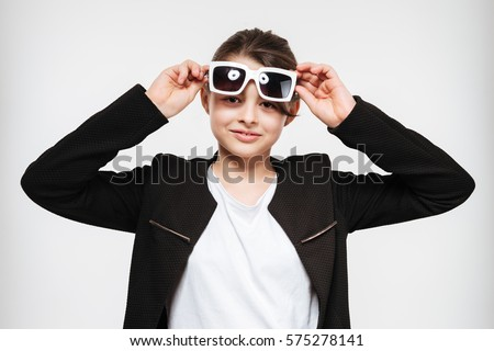 Image of cheerful young girl wearing sunglasses isolated over white background.