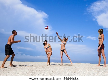 Image of cheerful young people on the beach playing volleyball. Great summer holidays.