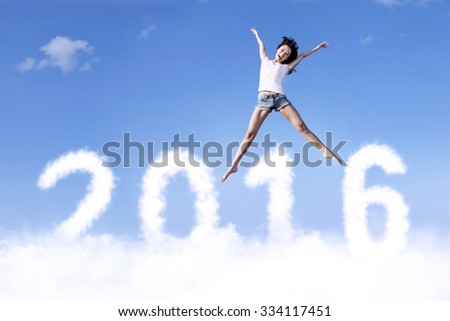 Image of cheerful young woman jumping and flying above clouds shaped numbers 2016 - stock photo