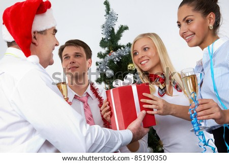 Image of cheering associates taking gifts from ceo in Santa cap at corporate party - stock photo