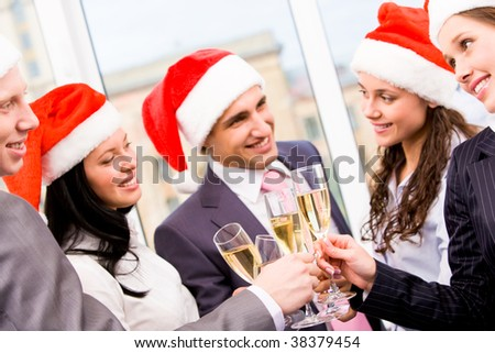 Image of cheering friends in Santa caps making toast at corporate party - stock photo