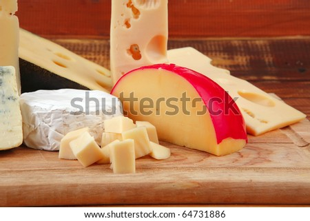 image of cheeses on wooden plate over table - stock photo