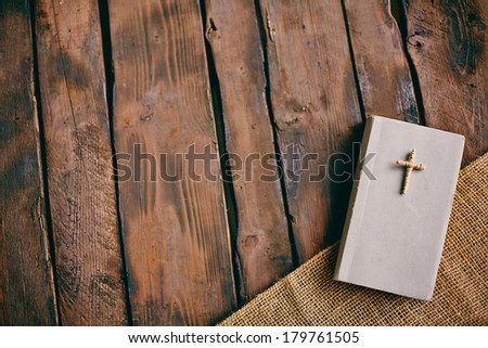Image of Christian book with cross on its cover on wooden background  - stock photo