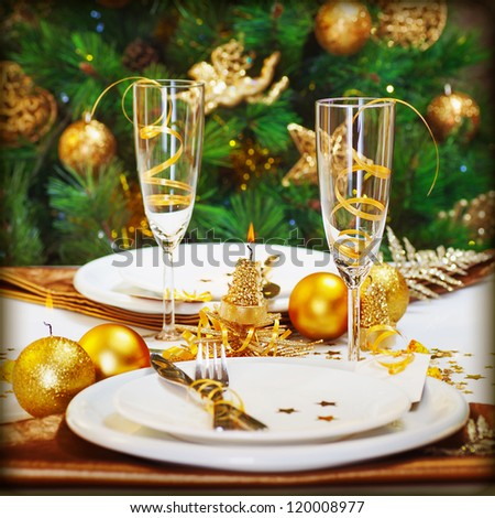 Image of Christmas dinner in restaurant, Christmastime table setting over decorated fir tree background, white plates served with knife and fork, two glass for champagne decorated with golden ribbon