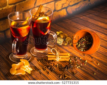 Image of christmas hot mulled wine with cinnamon, cardamom, anise and oranges on on wooden background
