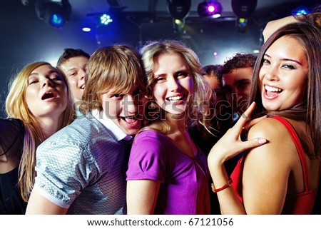 Image of clubbing friends looking at camera during party