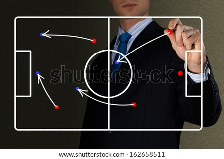 image of coach draws a diagram of a football game - stock photo