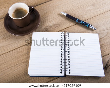 image of coffee cup with notebook and pen. - stock photo