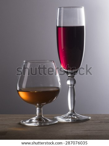 Image of cognac and wine glass on wood background grey. - stock photo