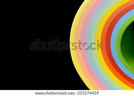Image of colorful curved sheets of paper shaped like a fan, on oblack background. - stock photo