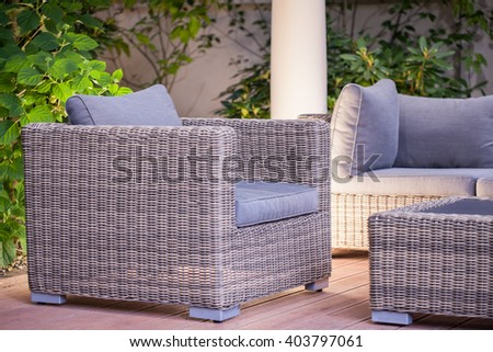Image of comfortable fashionable rattan armchair standing in patio - stock photo