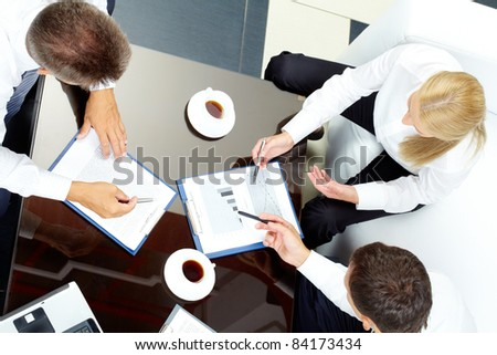 Image of company of successful partners discussing business papers at meeting