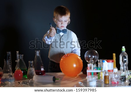 Image of concentrated pupil pierces balloon in lab - stock photo