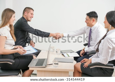 Image of concept of of successful handshake of business meeting and conference at office. A group of people busy working at the table with laptop. There are a multiracial people of asian and caucasian