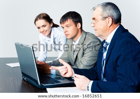 Image of confident boss explaining some computer work to coworkers