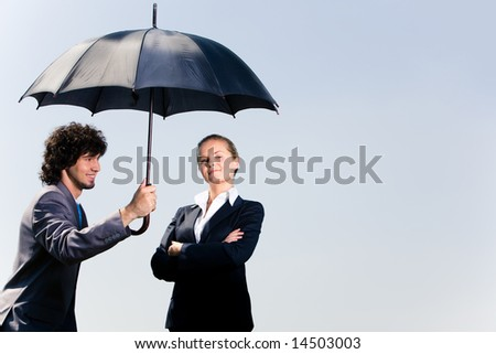 Image of confident business man holding umbrella and looking at woman on the background of sky - stock photo