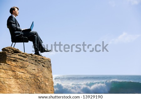 Image of confident business man sitting on the top of rock with laptop and looking at sea below - stock photo