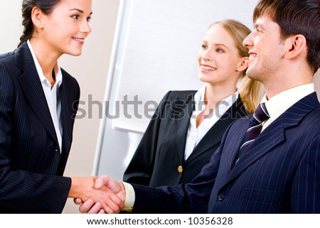 Image of confident business partners shaking hands in the office - stock photo