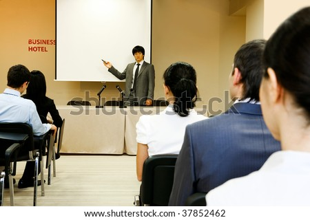 Image of confident businessman explaining something on whiteboard during conference