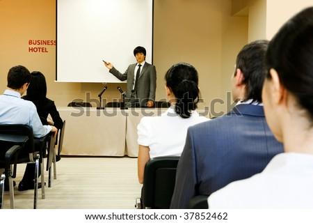 Image of confident businessman explaining something on whiteboard during conference - stock photo
