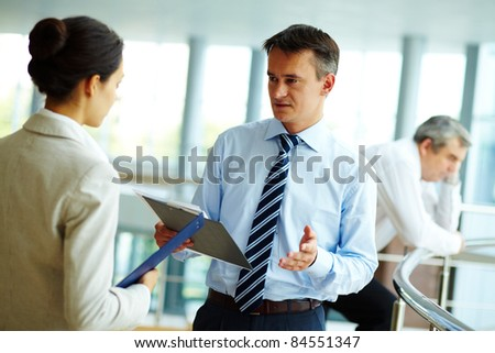 Image of confident businessman looking at partner while discussing new strategy - stock photo