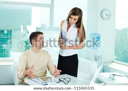 Image of confident businessman looking at pretty colleague while explaining his idea - stock photo