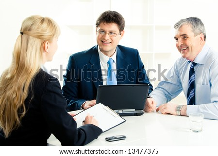 Image of confident businessmen looking at young secretary during meeting while discussing their work - stock photo